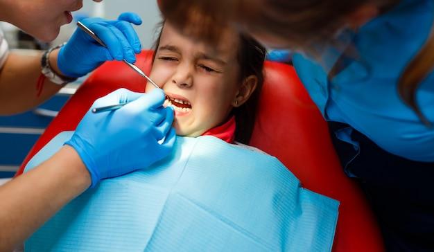 Behandlung im büro eines kinderzahnarztes, um die zähne eines kleinen mädchens zu versiegeln