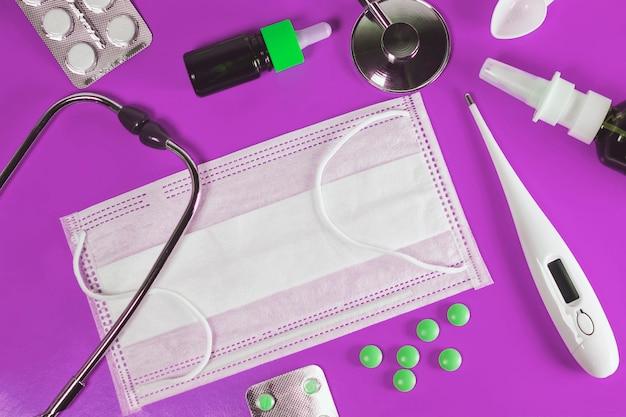 Behandlung von erkältungen und grippe. krankheitstag und medizinisches urlaubskonzept. verschiedene medikamente, ein thermometer, sprays aus einer verstopften nase auf blauem hintergrund, traditionelle medizin und grippekonzept. medizin flach.