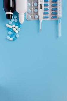 Behandlung von erkältungen und grippe. verschiedene medikamente, ein thermometer, spritzt aus einer verstopften nase und ein rachenschmerz auf ein blaues. copyspace. medizin flach liegen