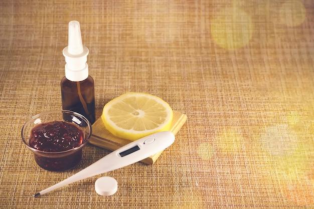 Behandlung von erkältungen und grippe. verschiedene medikamente, thermometer, erkältungspillen, rachenspray, nasentropfen, zitrone auf braunem hintergrund. behandlung von grippe. platz kopieren. medizin flach.