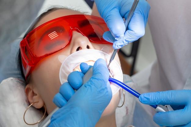 Behandlung von kariösen zähnen. der arzt benutzt einen spiegel am griff und eine bor-maschine