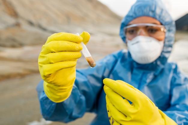 Behandschuhte hände einer jungen ökologin in atemschutzmaske und brille, die eine flasche mit einer probe schmutzigen wassers aus verschmutztem und toxischem bereich hält