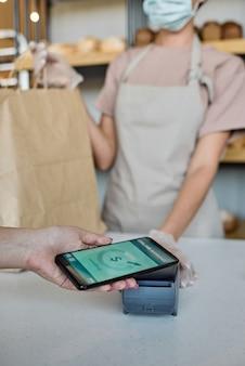 Behandschuhte hand einer bäckerin, die eine papiertüte hält, während der kunde mit dem smartphone bezahlt