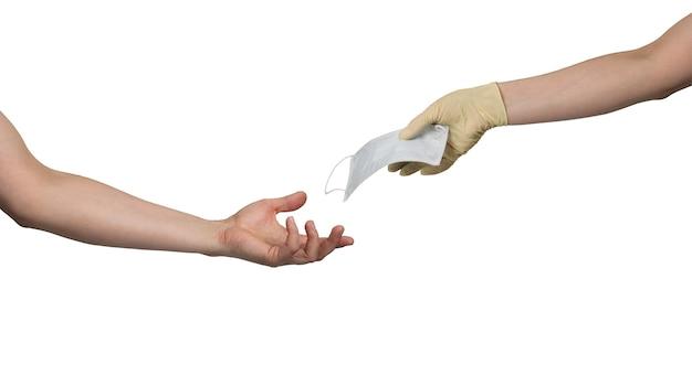 Behandschuhte hand gibt medizinische gesichtsmaske, um einer anderen person zu übergeben Premium Fotos