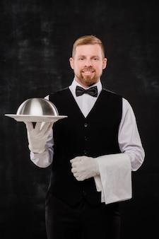 Behandschuhter junger kellner in fliege und schwarzer weste, der cloche mit essen und sauberem weißem handtuch für einen der kunden des restaurants hält