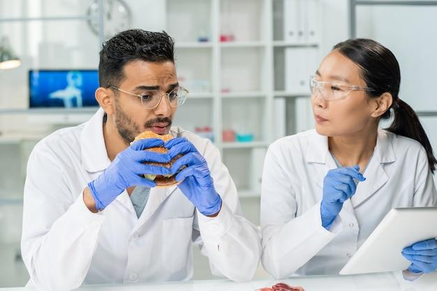 Behandschuhter junger männlicher arbeiter der lebensmittelkontrolle, der hamburger nach arbeitsplatz isst und seiner kollegin mit tablette im labor seinen geschmack beschreibt
