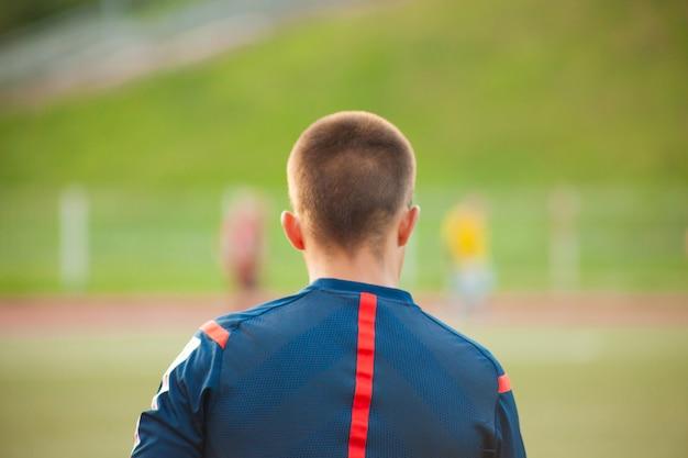 Behilflicher fußballschiedsrichter in einem fußballplatz mit spielern