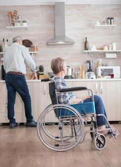 Behinderte ältere frau, die im rollstuhl in der küche sitzt und durch das fenster schaut. leben mit behinderten. ehemann hilft ehefrau mit behinderung. älteres ehepaar mit glücklicher ehe.