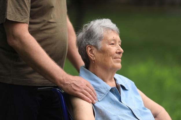 Behinderte ältere frau, die im rollstuhl nah oben sitzt