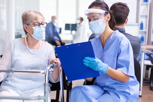Behinderte ältere frau, die mit einem facharzt über die behandlung im krankenhausflur mit gesichtsmaske gegen coronavirus diskutiert