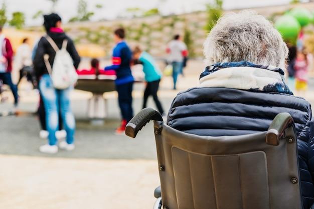 Behinderte ältere frau, die zurück zu rückseite in einem rollstuhl sitzt