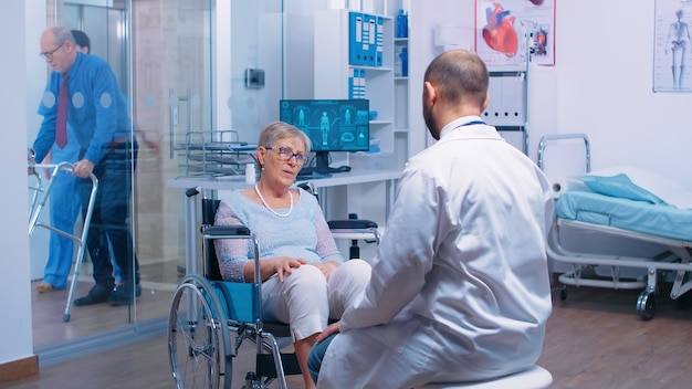Behinderte ältere frau im rollstuhl, die eine medizinische beratung durch einen arzt in einer modernen privatklinik oder einem krankenhaus sucht. erholungsbehandlung, hilfe für behinderte menschen. altenhilfe