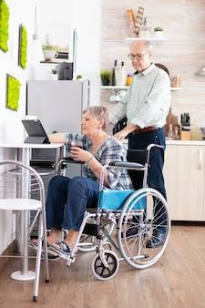 Behinderte ältere frau im rollstuhl mit tablet-computer in der küche mit ehemann in der nähe. gelähmte behinderte alte ältere person, die moderne online-internet-web-technologie verwendet.