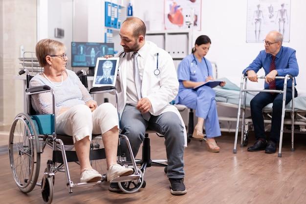 Behinderte ältere frau mit gehbehinderung, die im rollstuhl sitzt und mit einem arzt über einen tablet-pc spricht