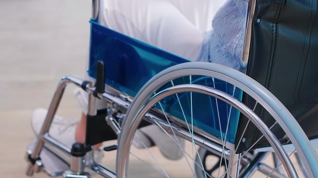 Behinderte alte frau, die hände auf stuhlrad im krankenhausflur hält. behandlung von krankheiten mit behinderungen, behinderungen, behinderungen, und patientenlähmung