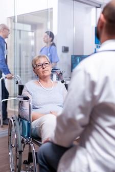 Behinderte alte frau, die während der ärztlichen untersuchung mit dem arzt im krankenzimmer im rollstuhl sitzt