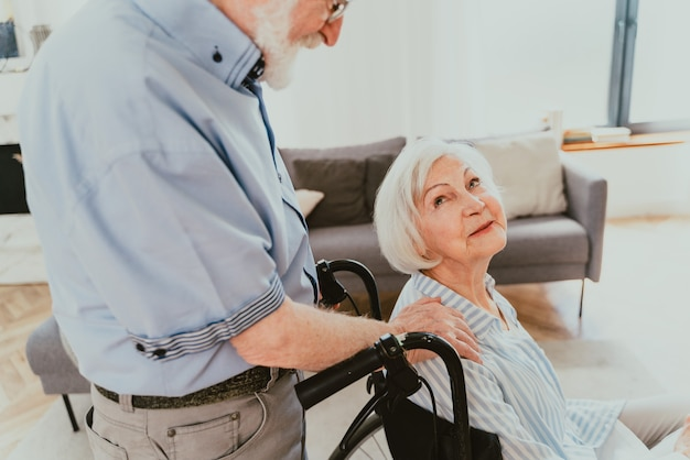 Behinderte alte frau im rollstuhl älteres paar zu hause partner, der aus dem krankenhaus zurückkommt