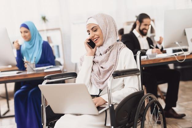 Behinderte arabische dame in hijab tätigt geschäftlichen anruf