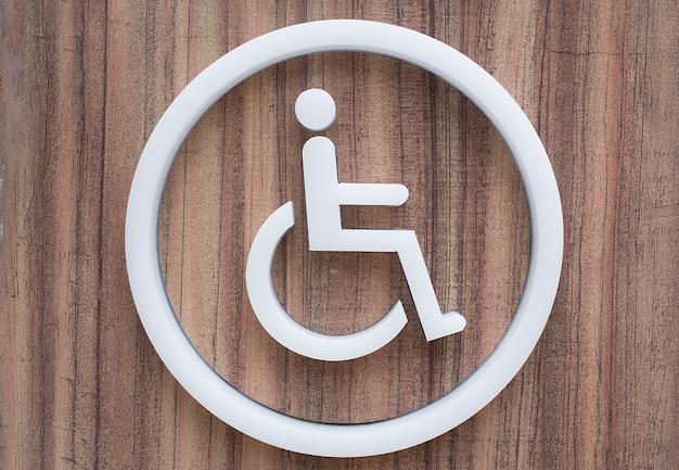 Behinderte badezimmer des weißen aufklebers auf dem bretterboden.
