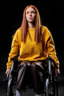 Behinderte behinderte rothaarige frau sitzt und schaut auf, träumt, hat gedanken. isolierter schwarzer hintergrund