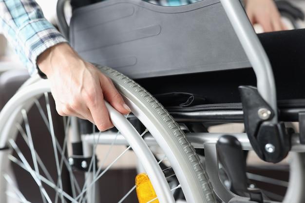Behinderte frau, die im rollstuhl sitzt und an radnahaufnahme festhält