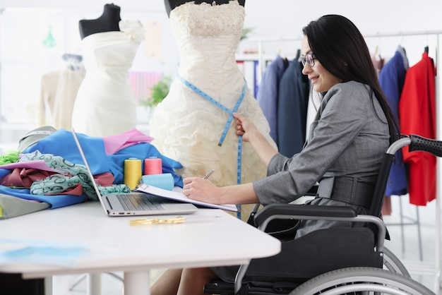 Behinderte frau im rollstuhl, die messungen vom hochzeitskleid nimmt.