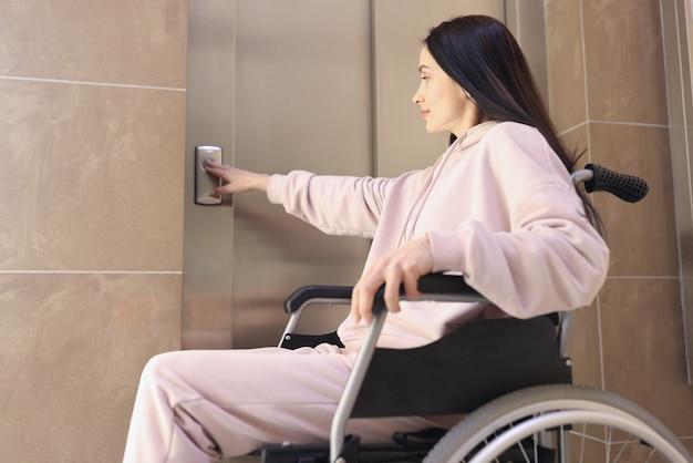 Behinderte frau im rollstuhl drückt ruftaste