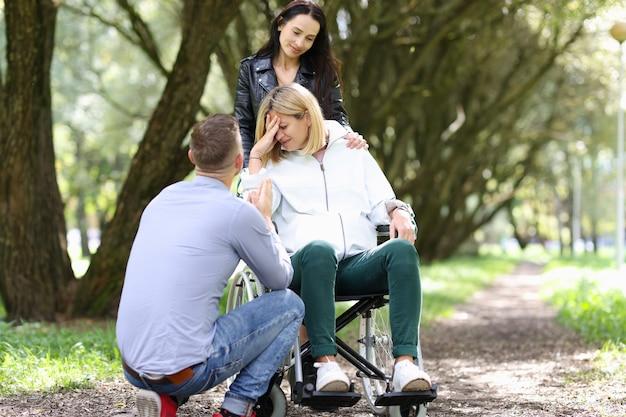 Behinderte frau im rollstuhl mit ihrem freund, der vor einem mann in parkschwierigkeiten weint