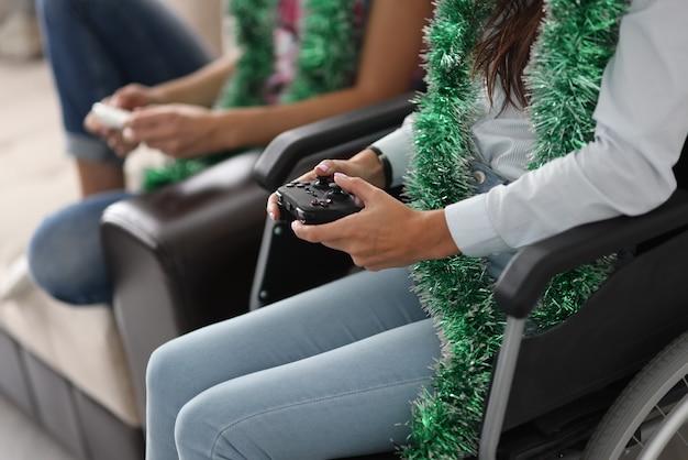Behinderte frau im rollstuhl und lametta um den hals hält joystick von der computerkonsole mit freund zu hause