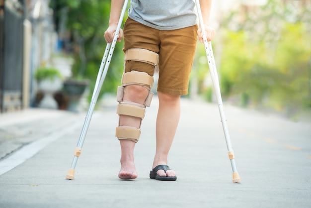 Behinderte frau mit den krücken oder spazierstock- oder kniestütze, die in der rückseite, halber körper stehen.