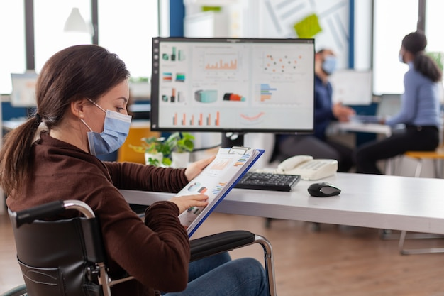 Behinderte geschäftsfrau mit schutzmaske, die in einem neuen normalen finanzunternehmen arbeitet, das auf dem pc tippt und berichte überprüft