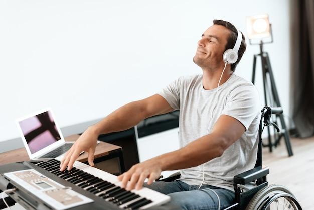 Behinderte im rollstuhl vor dem synthesizer