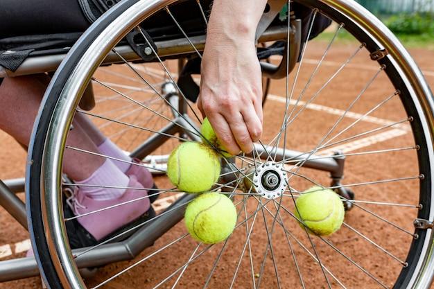 Behinderte junge frau auf dem rollstuhl, der tennis auf tennisplatz spielt. nahaufnahme einer hand nimmt einen tennisball, der in einem rad geregelt wird