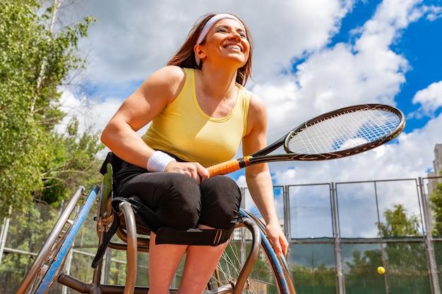 Behinderte junge frau auf dem rollstuhl, der tennis auf tennisplatz spielt.