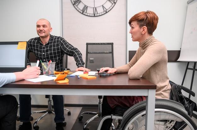 Behinderte junge frau im büro am schreibtisch