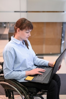 Behinderte junge frau im büro, die laptop betrachtet