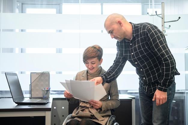 Behinderte junge frau im büro, die papiere betrachtet