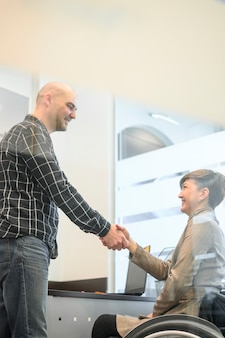 Behinderte junge frau im büro händeschütteln