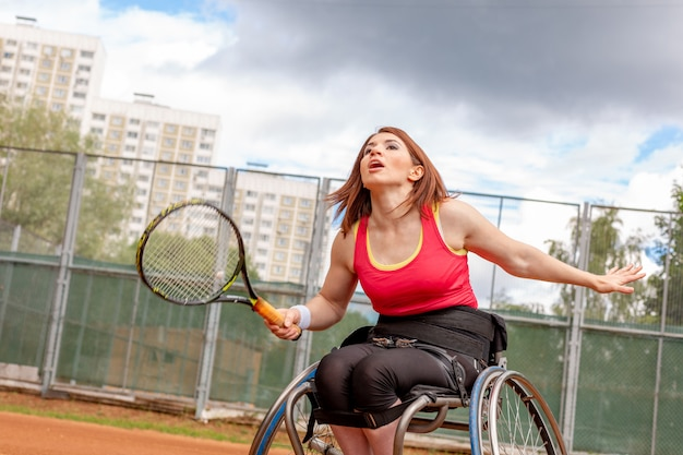 Behinderte junge frau im rollstuhl, die tennis auf tennisplatz spielt.