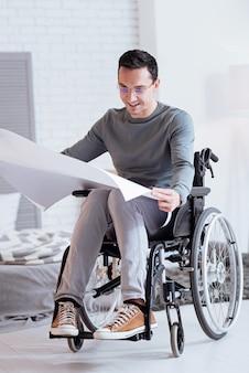 Behinderte person. attraktive brünette, die positivität ausdrückt und skizze hält, während sie es betrachtet