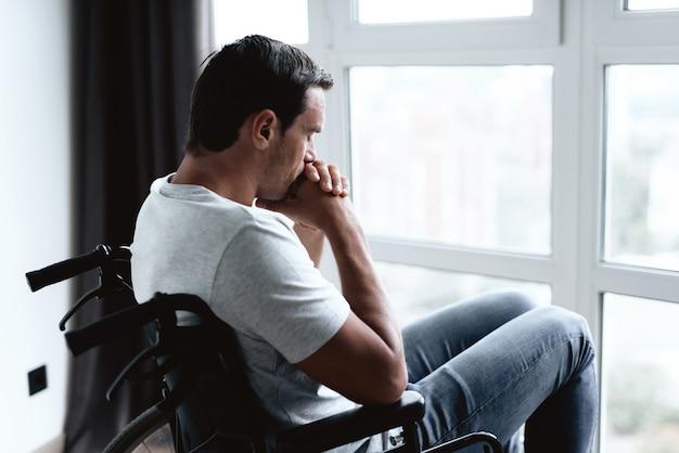 Behinderte person im rollstuhl, der fenster betrachtet.