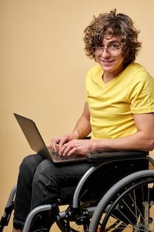Behinderte person in der freizeitkleidung, die mit laptop auf rollstuhl sitzt, lokalisiert über beige wand. gutaussehender lockiger mann genießt es, online zu arbeiten und nachrichten auf der tastatur zu tippen