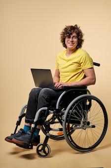 Behinderte person in der freizeitkleidung, die mit laptop auf rollstuhl sitzt, lokalisiert über beigem studiohintergrund. gutaussehender lockiger mann genießt es, online zu arbeiten und eine nachricht auf der tastatur zu tippen