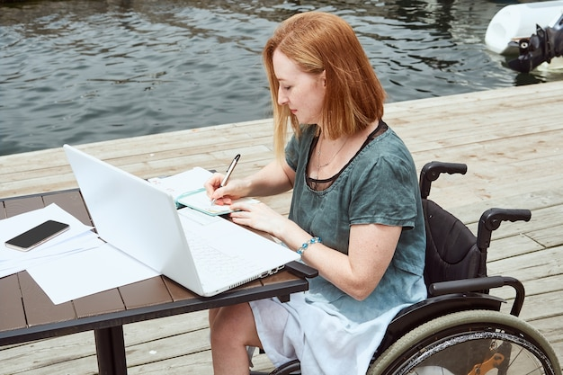 Behinderte rothaarige frau arbeitet aus der ferne mit laptop, macht notizen im notebook.