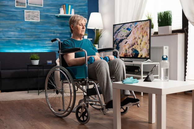 Behinderte seniorin im rollstuhl, die sich gymnastisches online-video auf einem tablet-computer ansieht und körpermuskeln mit hanteln trainiert