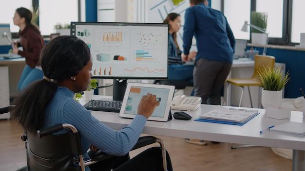 Behinderte unternehmerin mit bewegungsbehinderungen, die gleichzeitig computer und tablet verwenden, die im büro für unternehmensgründungen im rollstuhl sitzen