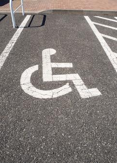 Behindertenparkplatz. zeichen der behinderunginfrastruktur. auf dem zementparkplatz. weiße linie.