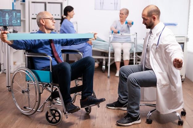 Behinderter älterer mann, der von einem arzt in einer modernen gesundheitseinrichtung von einem physiotherapeuten unterstützt wird
