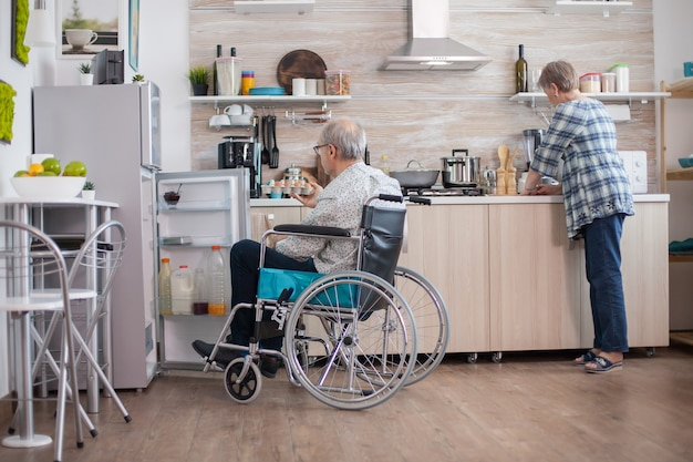 Behinderter älterer mann im rollstuhl, der eierkarton aus dem kühlschrank für die frau in der küche nimmt. ältere frau, die behinderten ehemann hilft. leben mit gehbehinderten menschen
