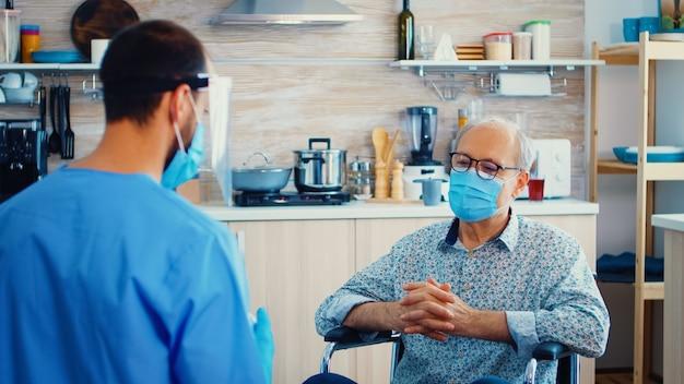 Behinderter älterer mann im rollstuhl, der während des hausbesuchs mit der pflegekraft über coronavirus diskutiert. sozialarbeiter, der behinderten älteren männern pillen anbietet. geriater hilft, die ausbreitung von covid-19 zu verhindern